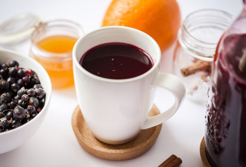 A white mug containing hot blackcurrant drink with blackcurrants and lemon in the background