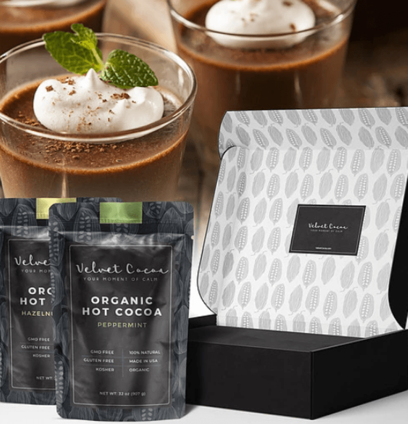 Velvet Cocoa hot chocolate box open in the lower right corner with two- two pound bags of hot cocoa sitting in front,  In the background are glass mugs of hot chocolate topped with whipped cream and garnished with grated chocolate and mint leaves