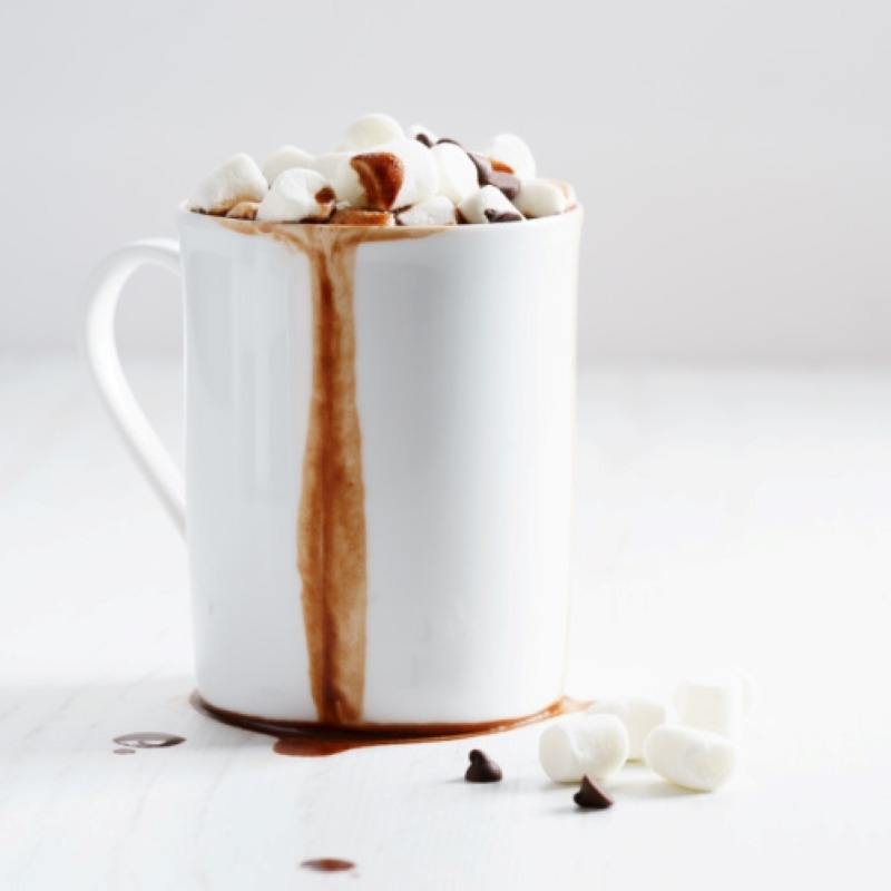 White mug overflowing with hot chocolate topped with mini marshmallows and mini marshmallows and mini chocolate chips scattered in front of the mug on the table