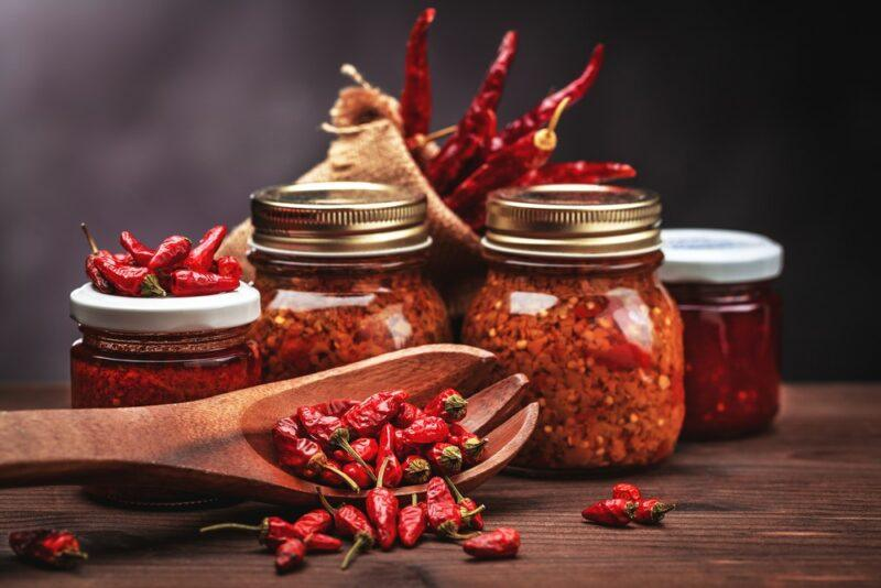 Various jars of hot peppers and hot sauces, next to a wooden spoon of the peppers