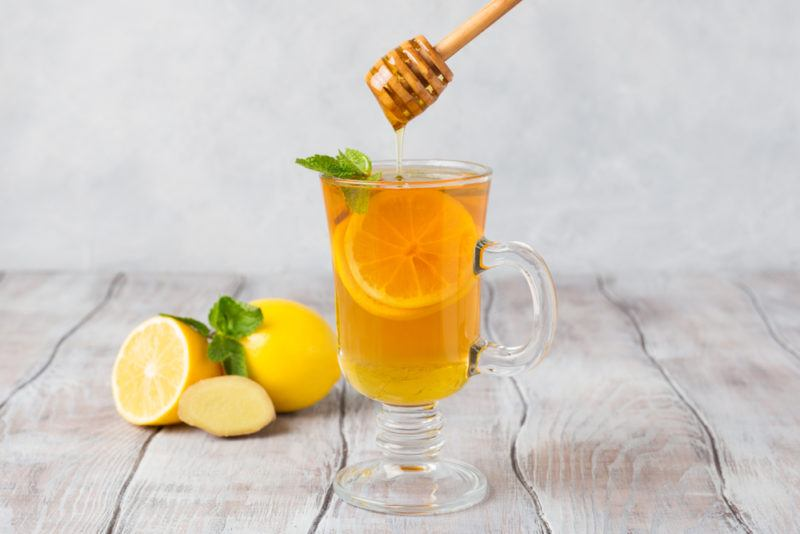 A glass mug containing lemon and honey with water