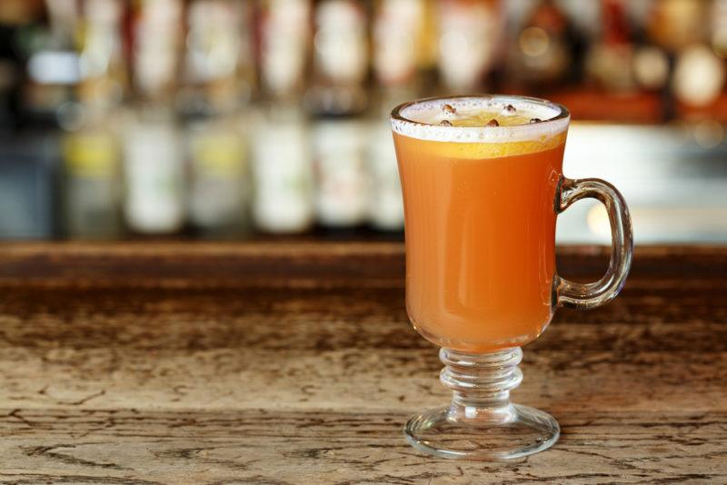 A glass mug containing a hot toddy in front of a bar