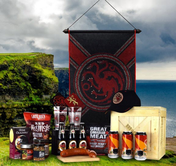 An outdoors image showing a House Targaryen banner, a hat, a crate, coasters and glasses, along with beer and snacks.