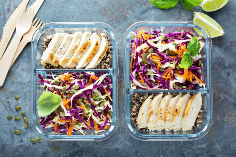 Two glass containers with couscous, salad and lean protein