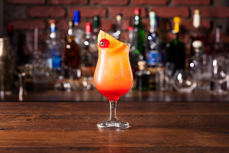 A Hurricane cocktail in focus with a bar in the background