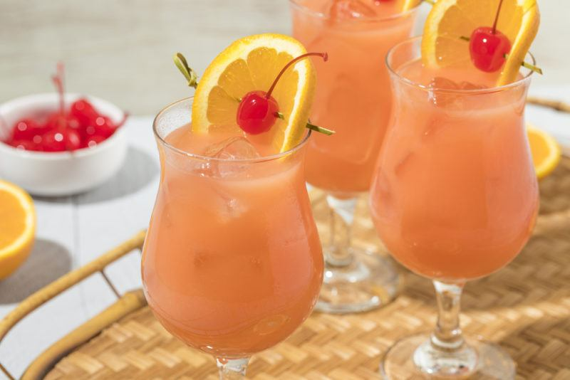 Three glasses of a hurricane cocktail with ice