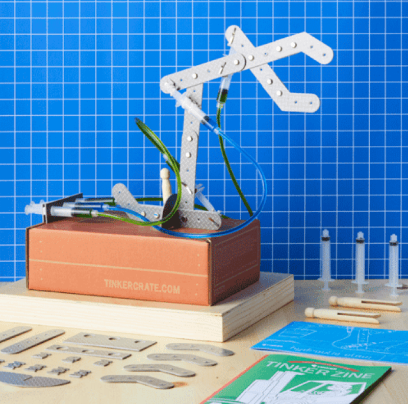 Hydraulic crane from the tinker crate from Kiwi Co. Shows tools, parts, and Tinker Zine book
