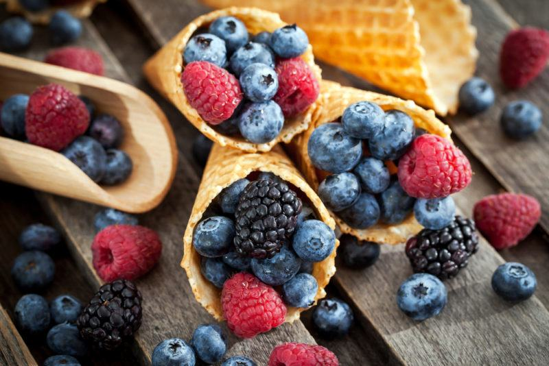 Three ice cream cones filled with berries, with more berries scattered around