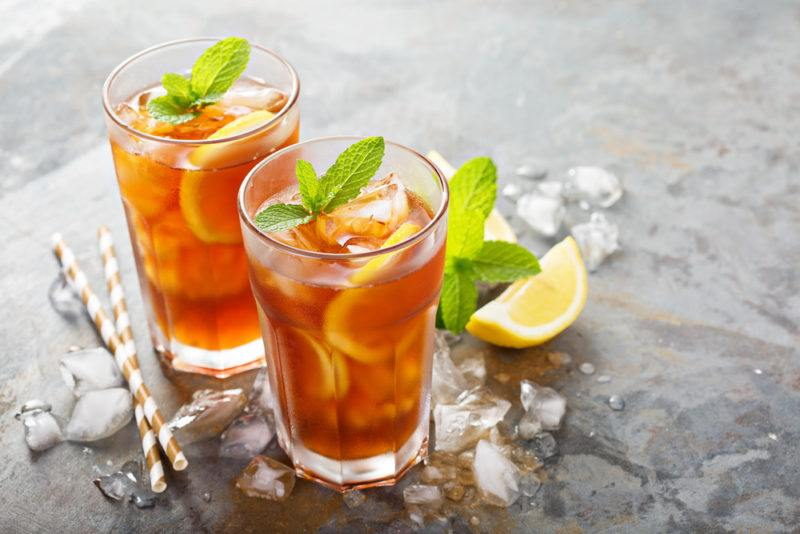 Two glasses of iced tea with lemon and mint on a table, with lemon, straw, mint and ice scattered around