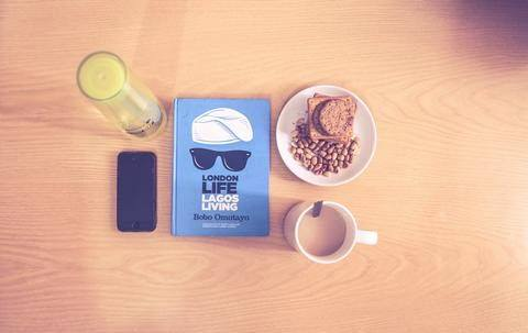 A table with food, coffee, a book and a phone