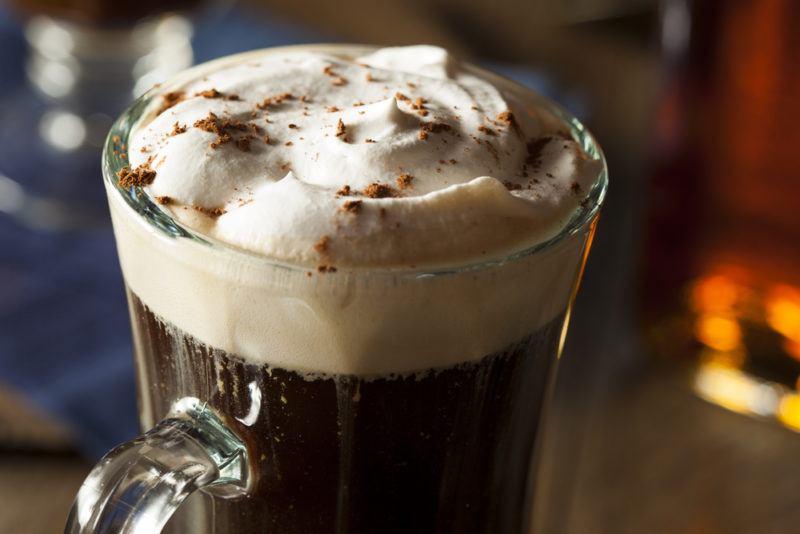 An Irish coffee in a glass mug with cream on top