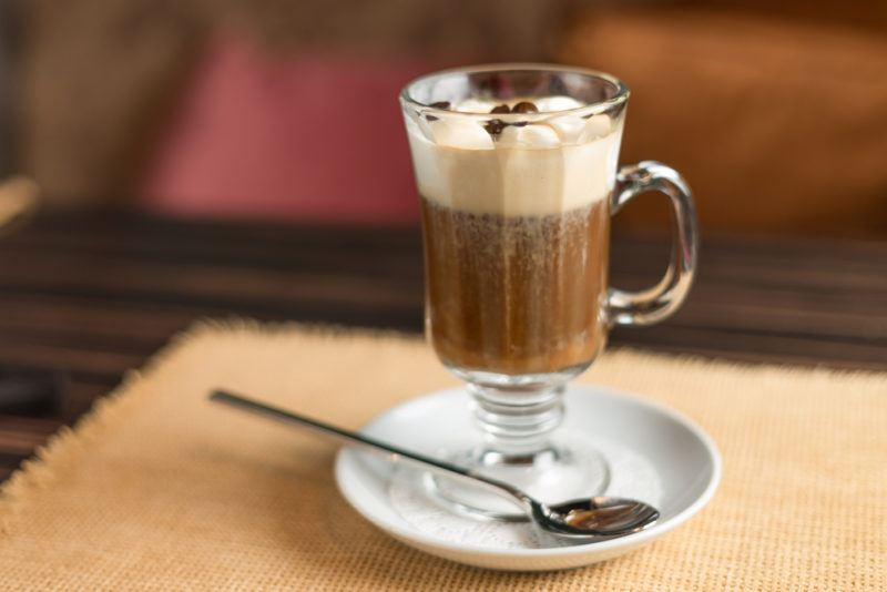 An Irish coffee cocktail in a glass on a saucer
