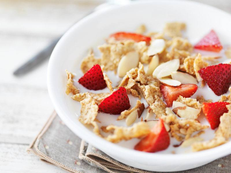 A white bowl containing cereal and sliced strawberries