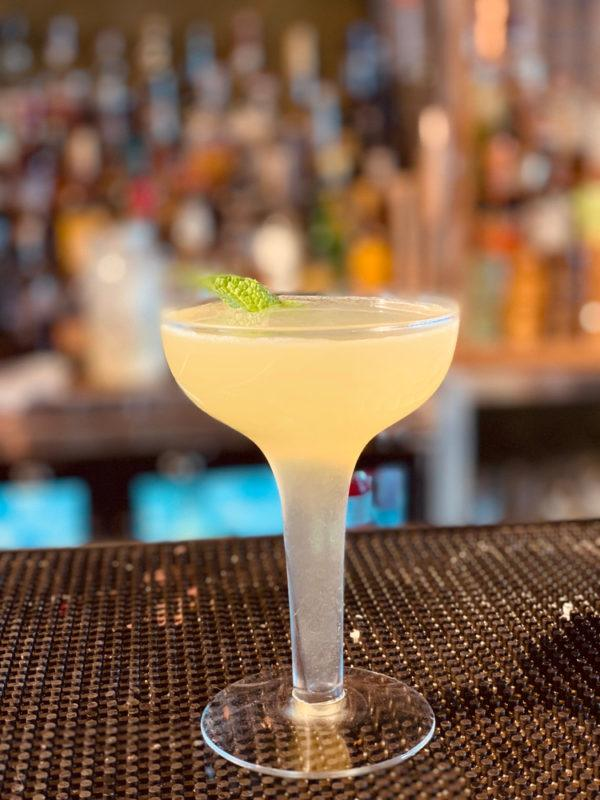 A yellow cocktail in a glass on a bar