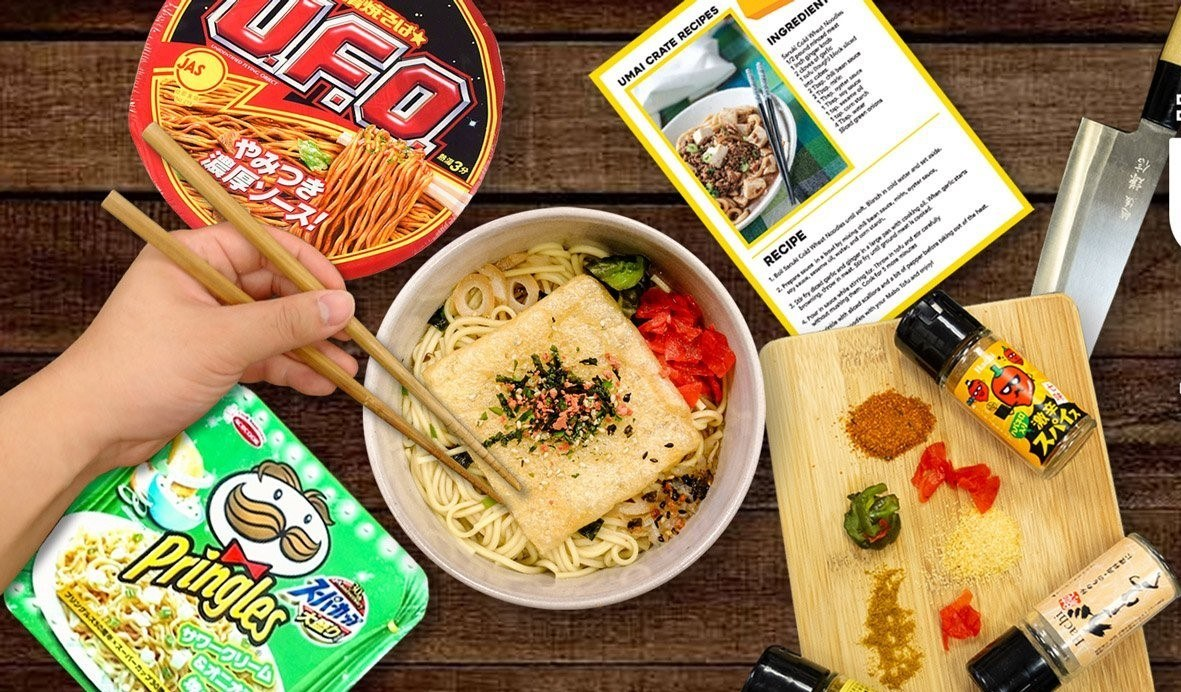wooden table with two packages of instant ramen (UFO and and Pringles) a white bowl with ramen topped with fresh vegetables and seasonings, in the upper right corner a recipe card, asian style chef knife, and a wooden cutting board in the lower right corner with fresh vegetables and seasonings