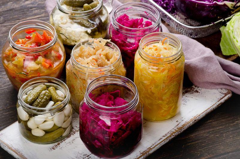 Multiple jars of fermented vegetables with salt