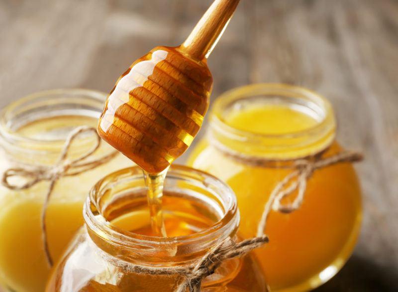 Three jars of honey with a stick