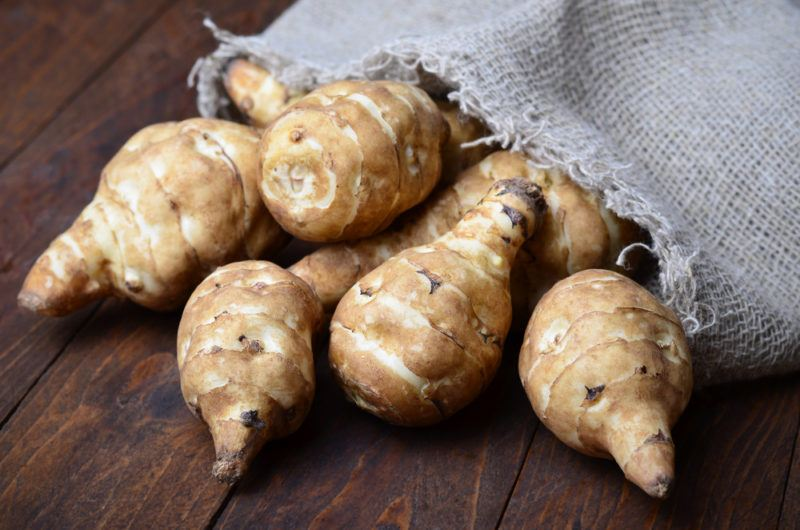 A selection of Jerusalem artichokes spilling out onto a wooden table