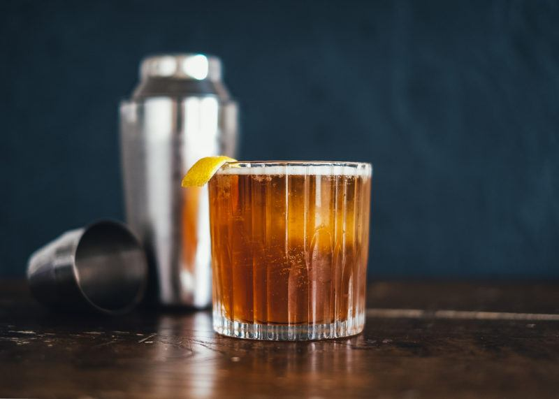 A Kahlua sour in front of a cocktail shaker