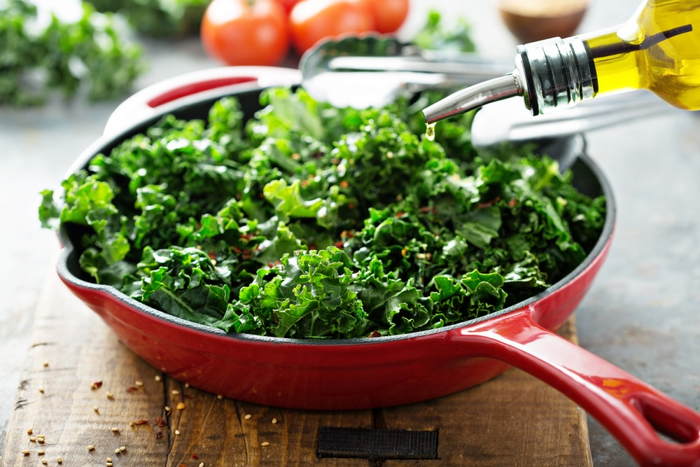 A red pan containg kale that is to be cooked