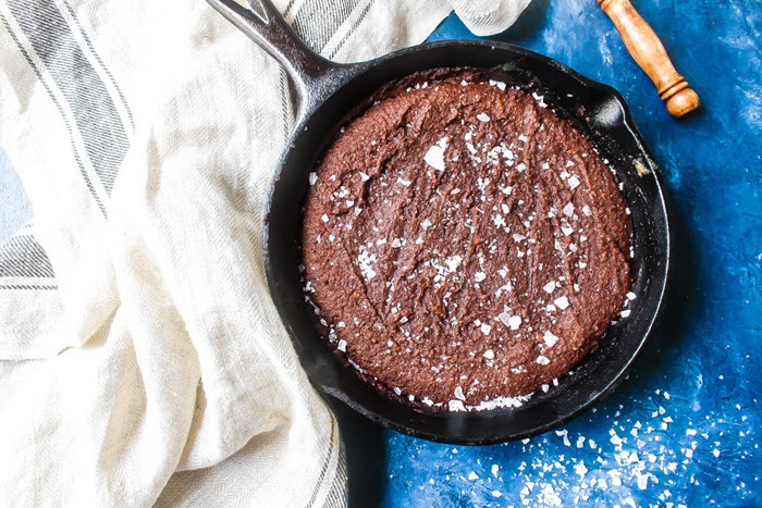 A cast iron skillet that contains a chocolate brownie with sea salt