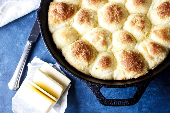 A cast iron skillet containing dinner rolls