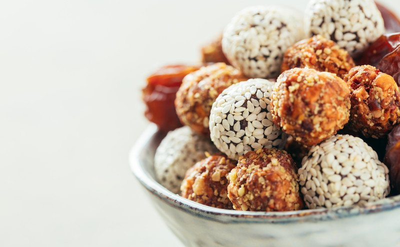 Several types of keto fat bombs rest in a bowl against a white background.