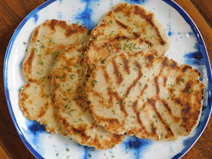 Various pieces of naan bread on a blue and white plate