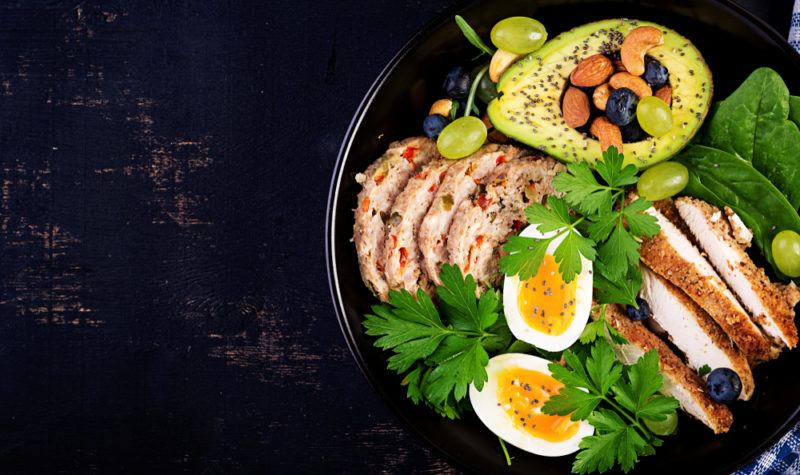 A keto protein bowl containing avocados, chicken, eggs, and greens
