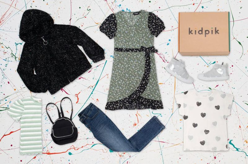 A selection of Kidpik clothing laid out against a white background with colorful detailing