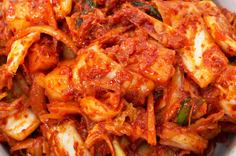This photo shows a closeup of kimchi, including pieces of cabbage and the red pepper sauce.