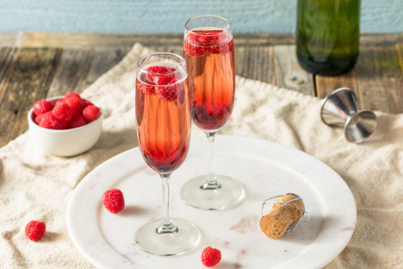 Two glasses of kir, with raspberries scattered around