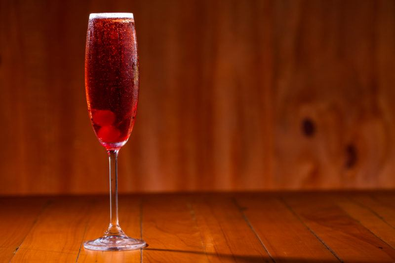 A kir royale cocktail on a wooden table against a wooden background
