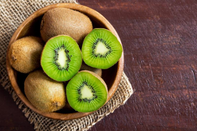 A bowl containing kiwis, some are whole, while others have been cut open