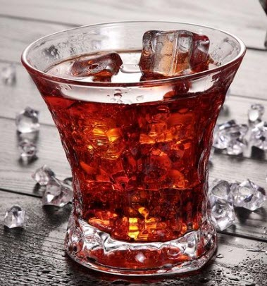 A whiskey glass with pieces of ice scattered around it