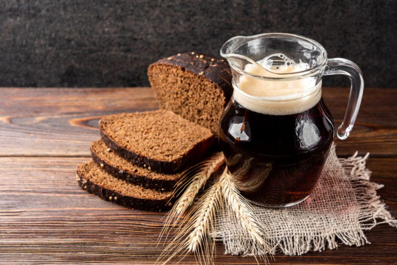 A jug of Kvass, some bread and some wheat on a wooden table