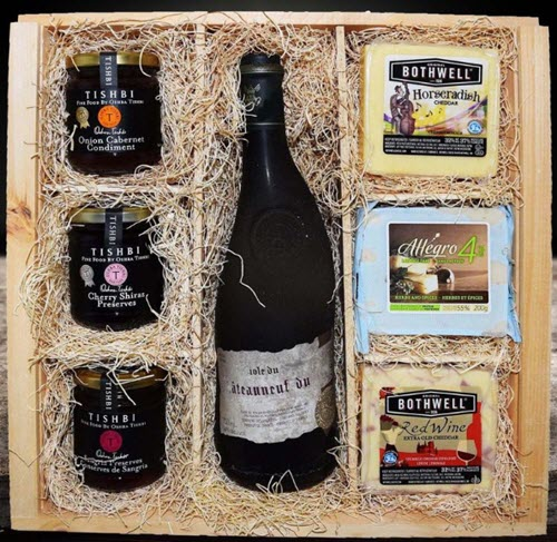 A packing crate with 3 pieces of cheese, 3 preserves and a bottle of wine