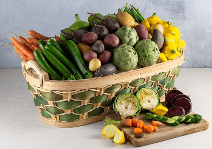 Baby vegetable basket.  The basket is a tan and green weaved basket filled with baby vegetables such as carrots, zucchini, tricolor potatoes, artichokes.  IN front of the basket is a wooden cutting board with sliced vegetables