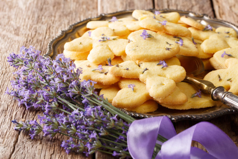 A metal tray of shortbread with lavender, next to stalks of lavender
