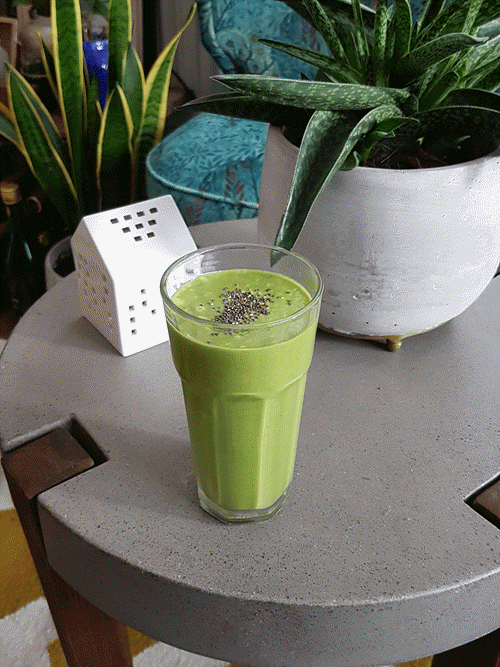 A green smoothie in a glass on a gray table