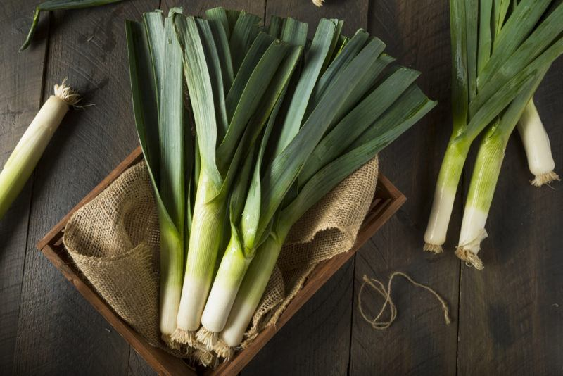 A wooden box with a cloth that contains fresh leeks and more leeks on a woodent table