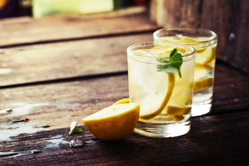 Two glasses of lemon water on a wooden table