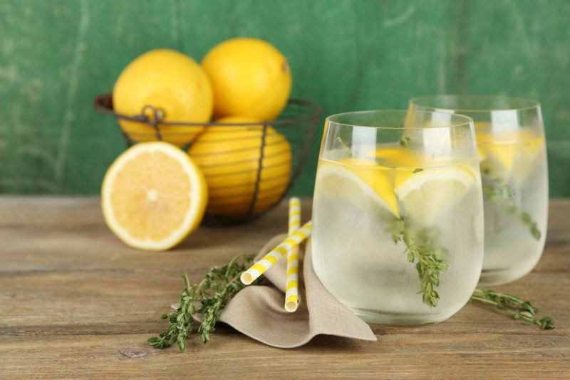 Two glasses with water, ice, lemon slices and herbs, with a container of lemons in the background
