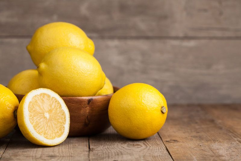 A small wooden bowl with whole lemons, along with a whole lemon and a lemon half on a table