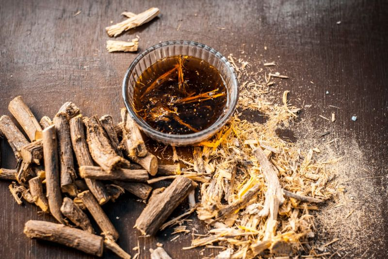 A mug of licorice root tea with dried licorice roots on the table.