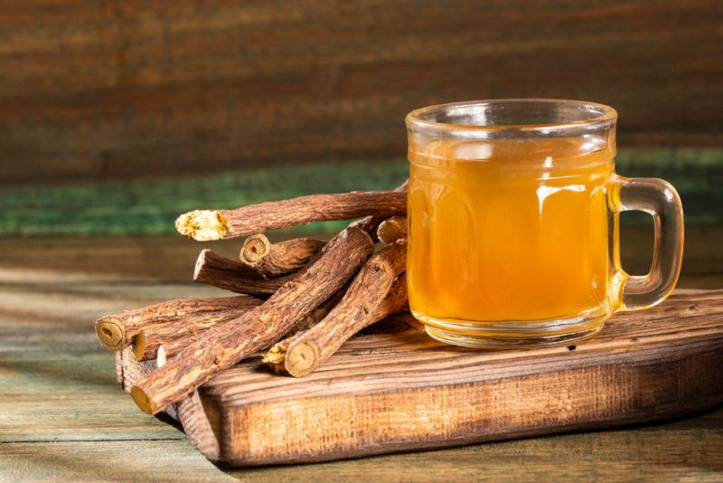 A mug of licorice tea with licorice roots on a wooden board