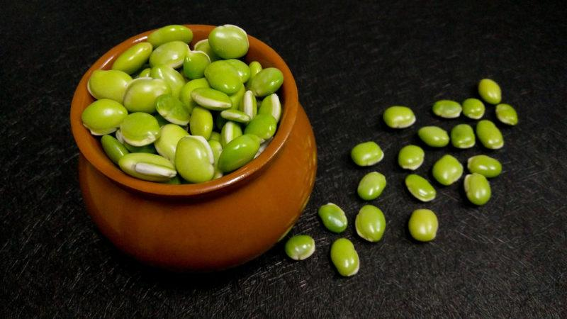 A brown bowl of lima beans and more lima beans on a table