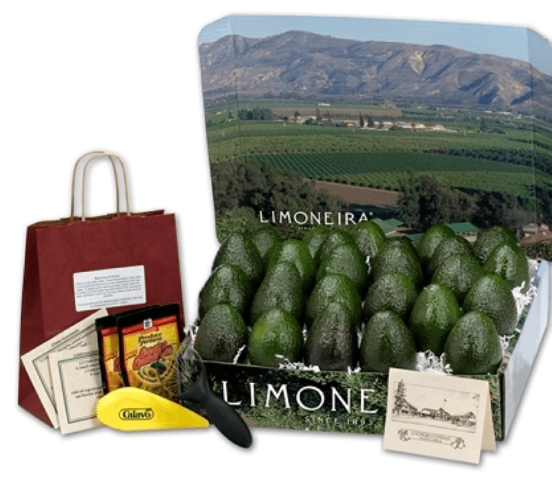 On the left side there is a red gift bag with seasoning packets and avocado kitchen accessories sitting in front, and two recipe cards.  In the center and right side of the picture is a large box of green avocados featured in a Limoneira box with a tent card standing next to the front right corner of the box