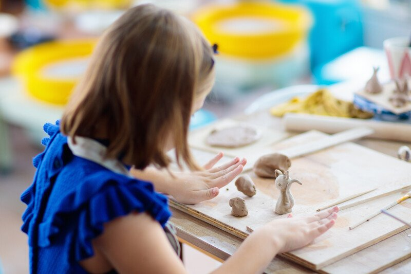 Craft of the Month Club for Kids - young girl at table working with clay shaping small figurines such as a cat