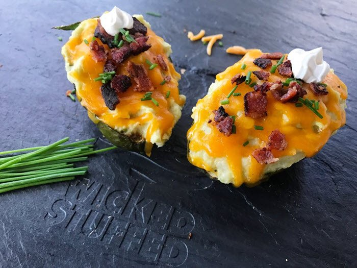 Two stuffed avocados filled with cheese, bacon and chives